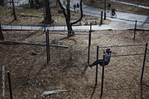 High angle view of male athlete hanging from monkey bars in forest