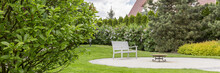 Well-kept Home Garden With A White Bench