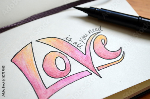 Photo  ALL YOU NEED IS LOVE hand lettering in notebook