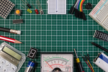 DIY Electrical Maker Tools Components On Green Cutting Mat Board. DIY Electrical Maker Tools With Copy Space For Text On Green Background. DIY Electrical Handmade Tools Electronic Maker Components.