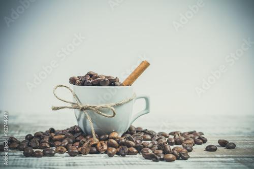 laska-cynamonu-i-biala-filizanka-z-ziarenkami-kawy-na-bialym-tle-na-drewnianym-stole