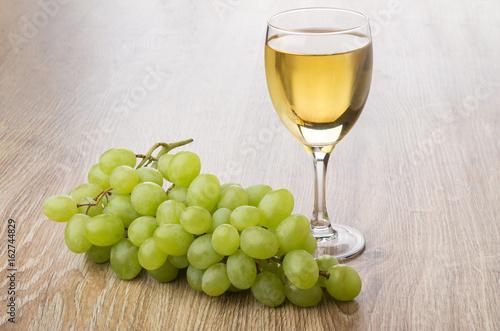 kieliszek-bialego-wina-i-kisc-winogron-na-stole