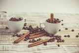 Fototapeta Kawa jest smaczna - Fragrant coffee beans in small cups and cinnamon sticks on a Provence-style table