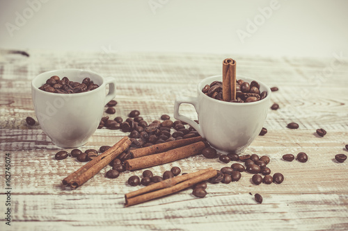 Fragrant coffee beans in small cups and cinnamon sticks on a Provence-style table