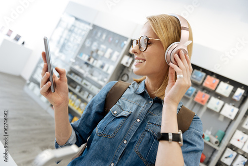 Recess Fitting Music store Smiling blonde lady using mockup headphones at shop
