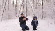 Young dad and his little son in the Park playing with the snow. Dad and his young son throw snow at the camera.