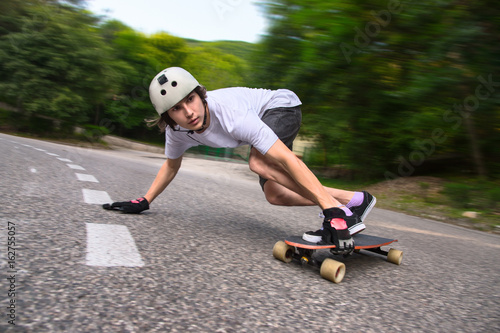 Young man is going to slide, slide with sparks on a longboard on the asphalt