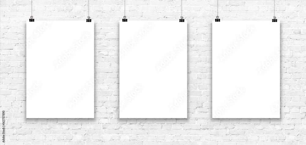 Fototapeta Three blank paper poster mockup on a white brick wall.