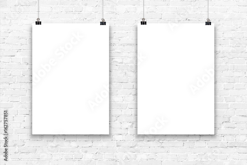 Photo Two blank paper poster mockup on a white brick wall.