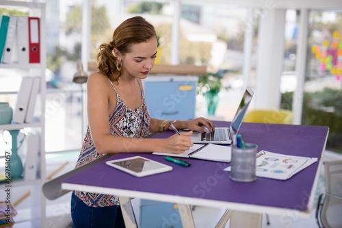 Fototapeta  Female executive working on laptop at desk