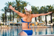 Woman in hat relaxing on the swimming pool. Girl at travel spa resort pool. Summer luxury vacation.