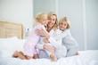 Portrait of smiling kids embracing her mother in bedroom