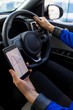 Close up of female customer using phone during test drive