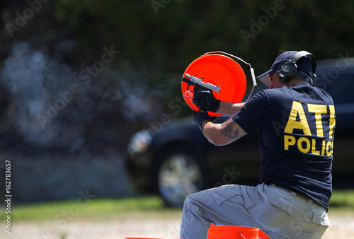 An ATF Officer fires a handgun used in crimes to collect casings to