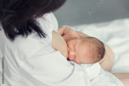 Mother breastfeeding newborn in the bed Canvas Print