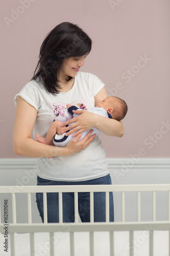 Photo  Mother with baby in cot