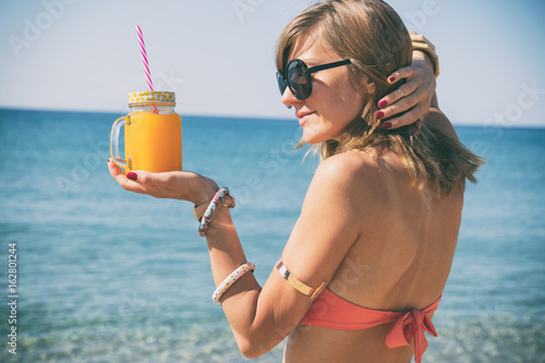Poster Lieu connus d Asie Cute woman holding juice in jar on the beach.