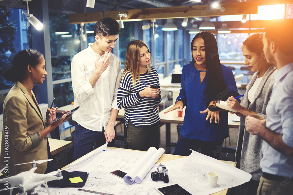 Fototapety, obrazy: Talented female architect teacher helping students with project for university coursework correcting mistakes in drawings and answer question during meeting in library with wifi zone and gadgets