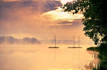 Fototapeta na wymiar Morning foggy lake landscape. Boats on the lake.