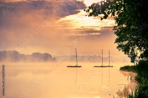 Obrazy na płótnie Canvas Morning foggy lake landscape. Boats on the lake.