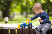 Portrait Of Cute Little Toddler Boy Playing With His Toy Tractor On A Playground On A Sunny Day. Child With Plastic Toy. Lifestyle