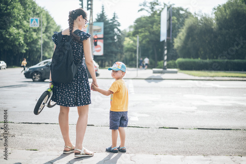 Fotografia, Obraz  mother with son stands on traffic light