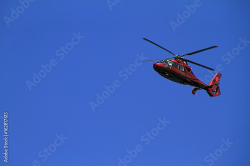 Staande foto Red helicopter flies in blue sky
