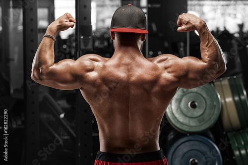 Plakat Tylni widoku mięśniowy mężczyzna pozuje w gym, seans plecy i bicepsach. Silny męski nagi tors, wypracowany