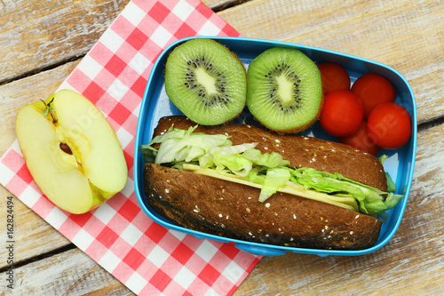 In de dag Assortiment Packed lunch consisting of bread roll with cheese and lettuce, cherry tomatoes and fresh fruit