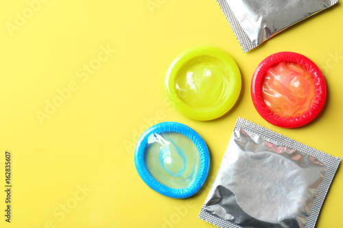 Fotografía Open and wrapped condoms on color background. Safe sex concept