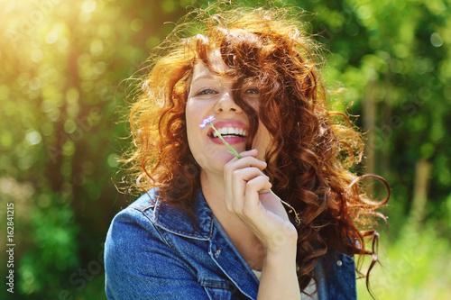 Fotografie, Obraz  jeune et jolie femme rousse souriante dans nature avec fleur bleue