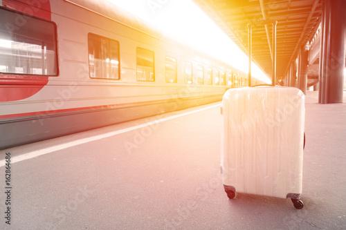 Zdjęcie XXL Biała podróż walizka na platformie przy stacją kolejową