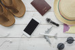 Top view essential accessories to travel concept.items for trip slipper,notebook,map,passport airplane,mobile phone,sunglasses on rustic wooden table background.