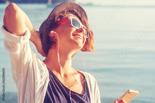 Papiers peints Magasin de musique Young beautiful woman hipster traveler in headphones and with mobile phone in hands, on the beach in the sun