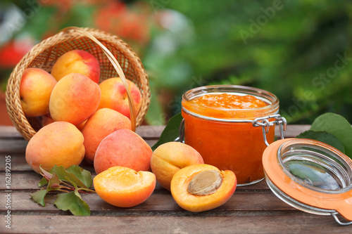 Foto Wicker basket full of ripe apricots and apricot jam in a jar