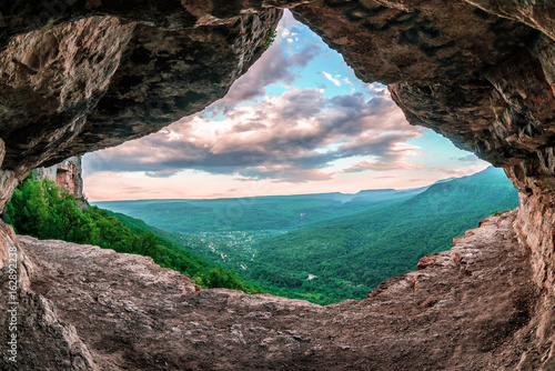 Beautiful scenic summer landscape view of Mezmay village from inside a weird rocky grotto in Caucasus mountains, Lenina Rock shelf, Russia