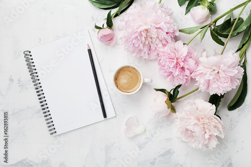 Obraz Morning coffee mug for breakfast, empty notebook, pencil and pink peony flowers on white stone table top view in flat lay style. Woman working desk. - fototapety do salonu