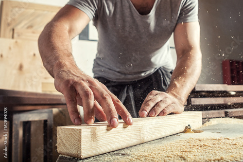 man  steals a wooden with a milling machine Fotobehang