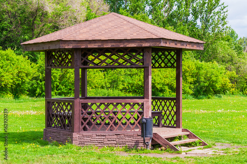 Fotografiet Wooden arbour a background of green trees