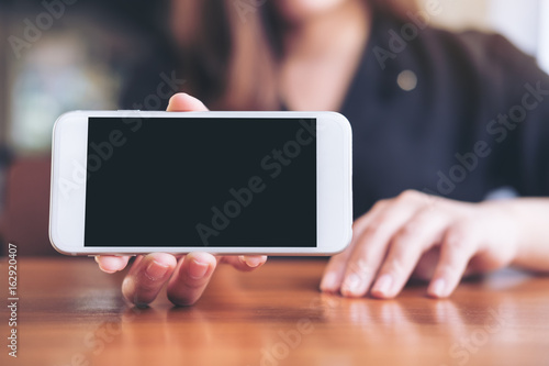 Fotografiet  Mockup image of a woman holding and showing white horizontal mobile phone with b