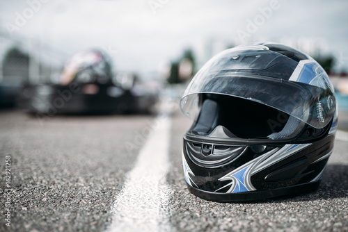 Photo sur Toile Motorise Racer helmet on asphalt, karting sport concept