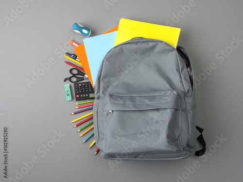06a6f4b0e1ca Top view of a backpack and school supplies on grey wooden table ...