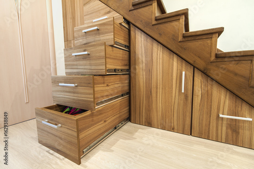 Foto op Plexiglas Trappen Modern architecture interior with luxury hallway with glossy wooden stairs in modern storey house. Custom built pullout cabinets on glides in slots under stairs