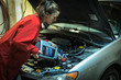 Female mechanic topping up the oil in a car