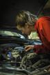 Female mechanic inspecting car engine