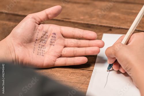 Foto People cheating on test by writing answer on hand