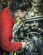 Female mechanic inspecting car engine with wrench