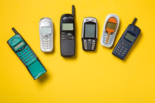 Old Mobile Phones On Yellow Ba...