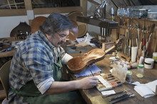 Violin Maker Painting Violin In Workshop
