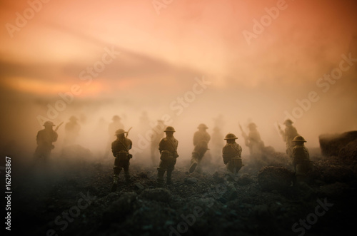 Obraz War Concept. Military silhouettes fighting scene on war fog sky background, World War Soldiers Silhouettes Below Cloudy Skyline At night. Attack scene. Armored vehicles. Tanks battle - fototapety do salonu